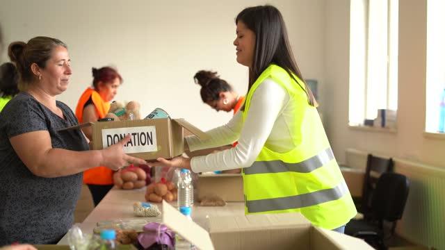 persone bisognose di ricevere una scatola di donazione di cibo da un volontario - beneficenza video stock e b–roll