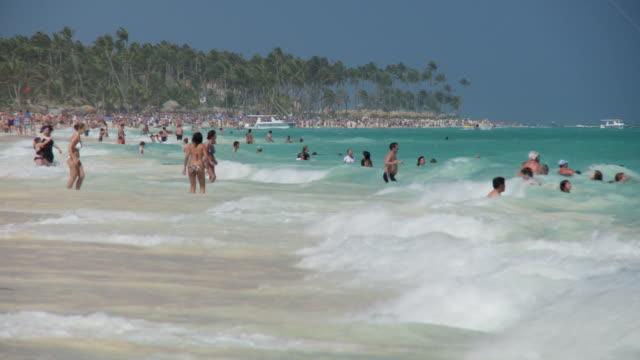 vídeos y material grabado en eventos de stock de ws, people in ocean waves, punta cana, dominican republic - hispaniola