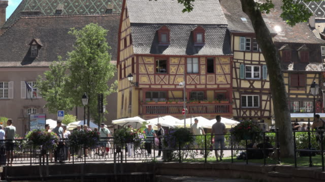 People in old town with half-timbered house in Colmar