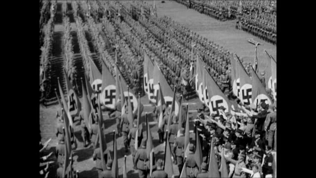 people in open bleachers w/ arms extended in nazi salute w/ soldiers standing below ws large nazi germany flags moving between ranks angled ws people... - ナチズム点の映像素材/bロール