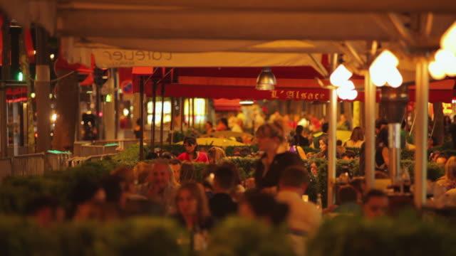 vidéos et rushes de ms selective focus people in outdoor restaurants on champs-elysees at dusk, paris, france - restaurant