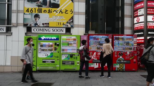 people in protective face masks passing vending machines in shibuya, shinjuku and kagurazaka district in tokyo, japan, on sunday, october 11, 2020. - shinjuku ward stock videos & royalty-free footage