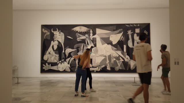 """people in protective masks walk by and look at the painting """"guernica"""" by pablo picasso during the partial reopening of the reina sofia museum as the... - art gallery stock videos & royalty-free footage"""