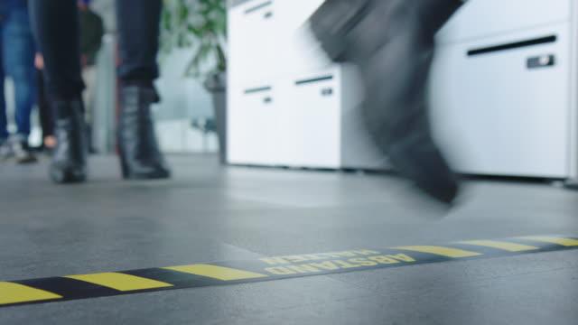 vídeos de stock e filmes b-roll de people in queue with social distancing at safe entry checkpoint in office - distante