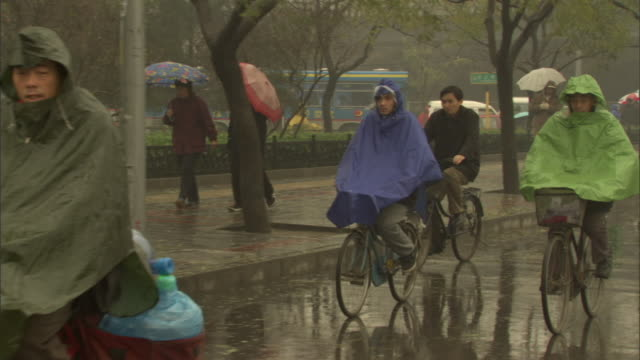 ms people in rain ponchos riding bicycles on rainy day, beijing, china - waterproof clothing stock videos & royalty-free footage