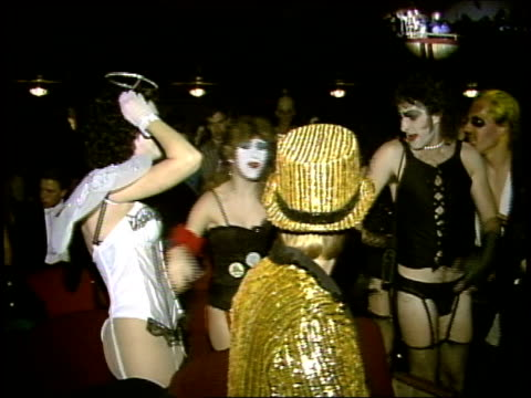 vidéos et rushes de people in rocky horror picture show costumes dancing in aisles at a screening - 1985