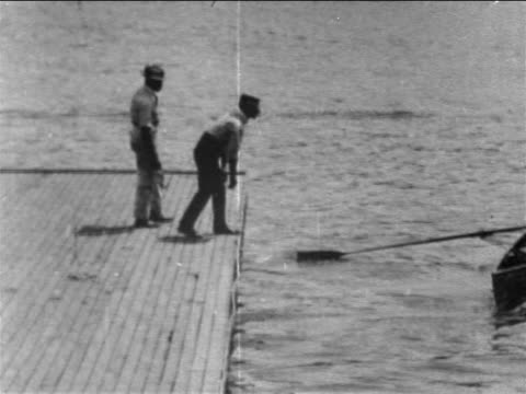 b/w 1905 people in rowboat taking off from dock / other boats pass in background / philadelphia / newsreel - rowing boat stock videos & royalty-free footage