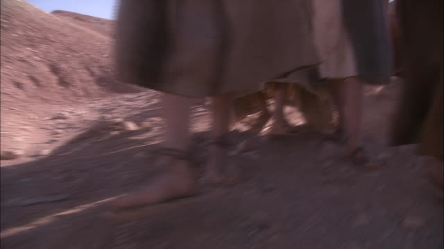 people in sandals and robes walk through the sahara desert. - convoy stock videos & royalty-free footage