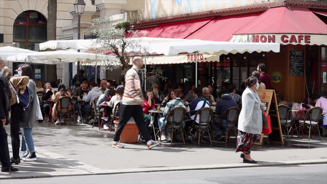 people in sidewalk cafes around 1pm. during the lunch break, in front of the entrance to the saiont antoine hospital . parisians adopt lifting of... - lunch stock videos & royalty-free footage
