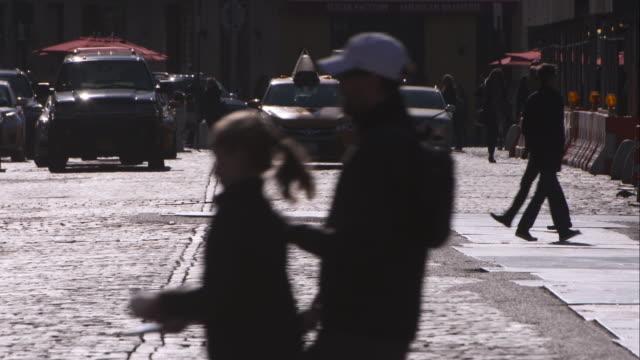 stockvideo's en b-roll-footage met people in silhouette cross the crosswalk at a manhattan intersection - kassei