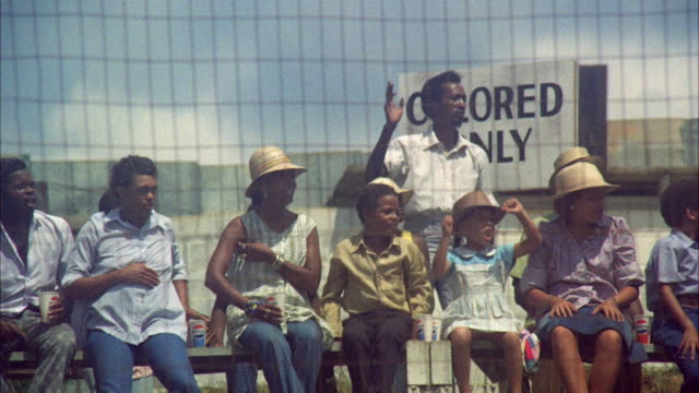 MS People in stadium watching car racing at Danville speedway, holding sign 'For Colored Only' / Georgia, USA