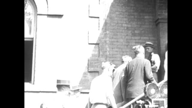 People in summer attire enter wroughtiron gate / LR Dudley Malone John Scopes Clarence Darrow / people climb stairs passing large camera / CU J W...