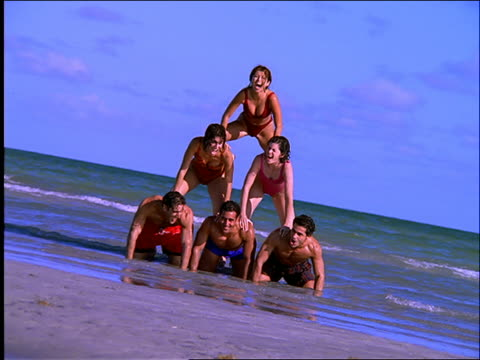 vídeos y material grabado en eventos de stock de people in swimsuits form human pyramid on beach / they fall at end of shot - traje de baño de una pieza