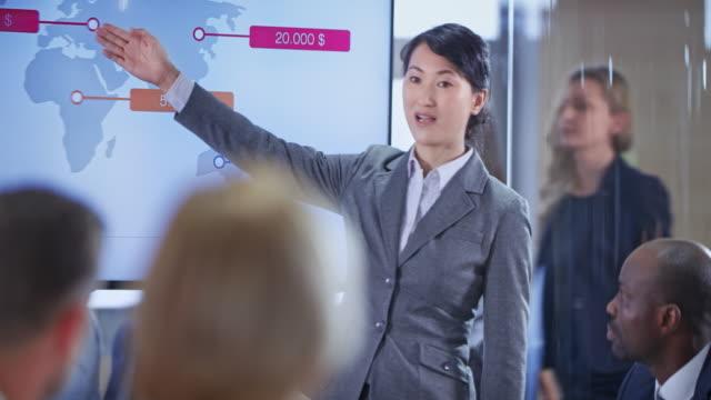 vídeos de stock, filmes e b-roll de pessoas na sala de conferências, ouvir uma apresentação realizada por seu colega asiática - portable information device