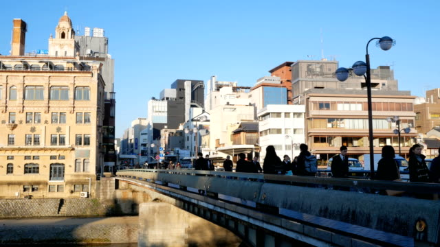 people in the morning at shijo bridge in kyoto japan - kyoto stock videos and b-roll footage
