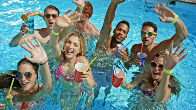 SLO MO People in the pool holding their drinks and waving for a video their friends is making