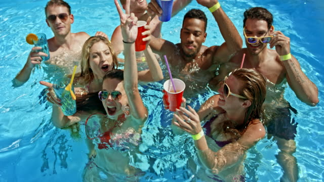 slo mo people in the pool making a toast into the camera - swimwear stock videos and b-roll footage