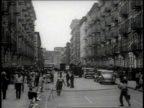 stockvideo's en b-roll-footage met 1938 ws people in the streets, children playing a game with paddles and a ball / new york city, new york, united states - 1938