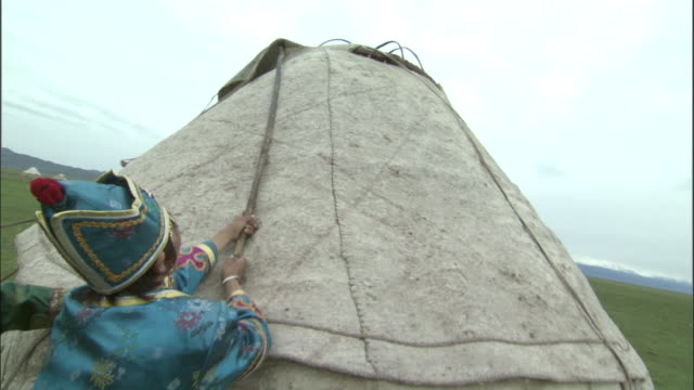 People in traditional clothes place felt onto roof of ger, Bayanbulak grasslands.