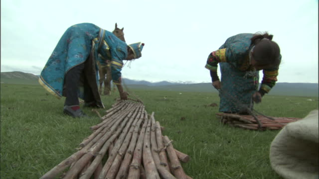 People in traditional clothes start to erect framework of ger, Bayanbulak grasslands,