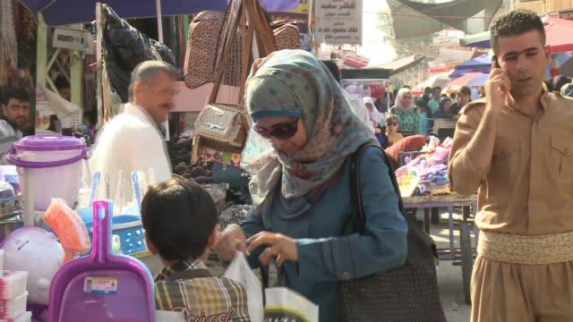 people in traditional clothing and contemporary clothing shop at kirkuk market. - 僧衣点の映像素材/bロール