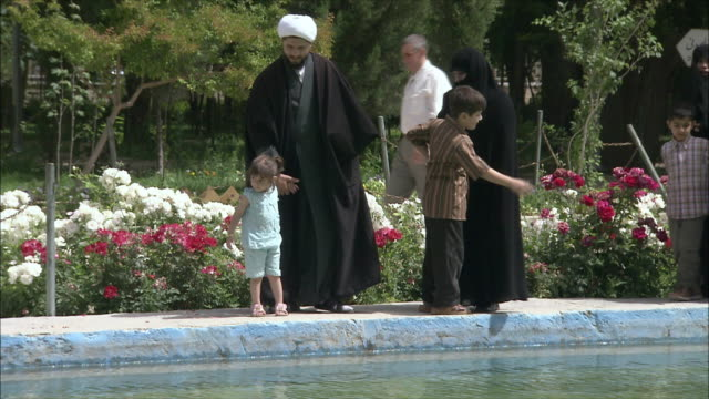 ms pan people in traditional clothing walking on edge of pool at chehel sotoun pavilion, isfahan, iran - burka stock videos and b-roll footage