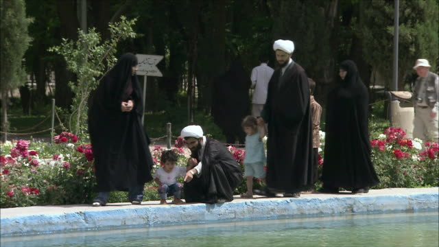 MS People in traditional clothing walking on edge of pool at Chehel Sotoun pavilion, Isfahan, Iran
