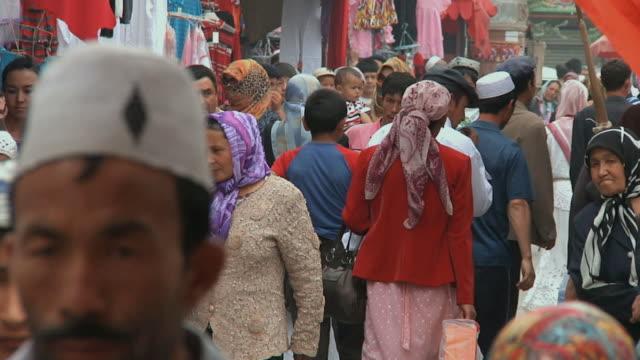slo mo ms people in traditional uighur clothing walking through market street / kashgar, xinjiang, china - 新疆ウイグル自治区点の映像素材/bロール
