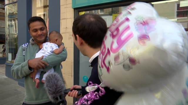 people in windsor await arrival of royal baby england berkshire windsor ext man and woman in union jack outfits shop front with royal baby clothes... - windsor england stock videos & royalty-free footage