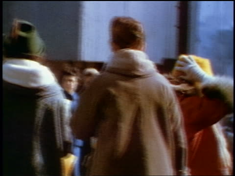 1957 pan people in winter coats + hats on city street / feature - 1957 stock-videos und b-roll-filmmaterial
