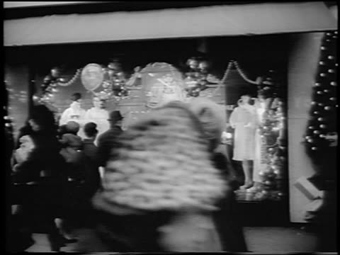 B/W 1964 people in Winter coats walking past Christmas display window / newsreel