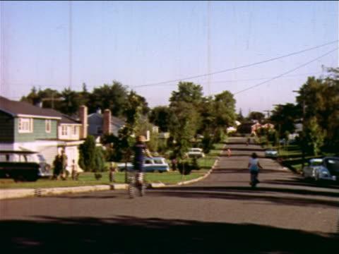 vidéos et rushes de 1957 people in yards, children running across street + riding bicycles on suburban street / nj - new jersey