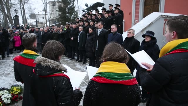 People including Lithuanian President Dalia Grybauskaite attend a state ceremony at Rasos Cemetery during the 100th anniversary of the restoration of...