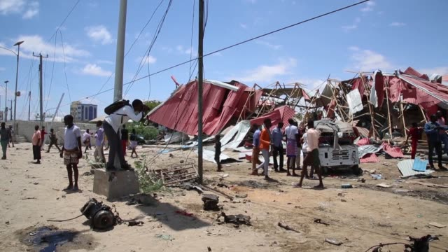 people inspect the site of a car bomb attack targeting a european union military convoy in mogadishu, somalia on september 30, 2019. al-shabaab... - somalia stock videos & royalty-free footage