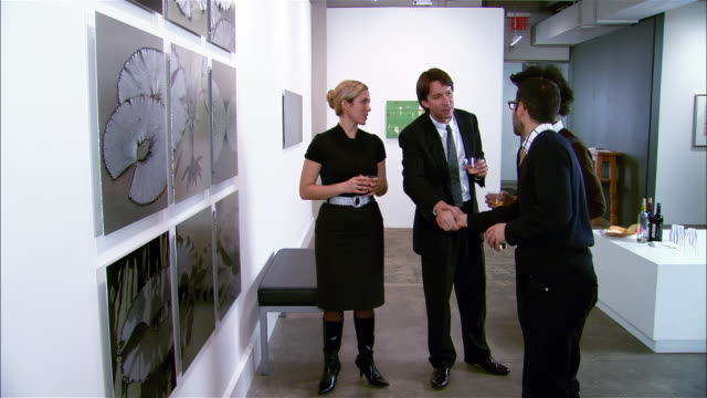 people introducing themselves and talking about artwork at gallery opening - 美術館点の映像素材/bロール