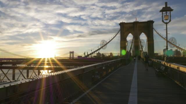 people jogging and biking on top of the brooklyn bridge at sunrise - brooklyn bridge stock videos & royalty-free footage