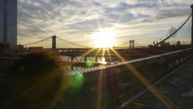 people jogging and biking on top of the brooklyn bridge at sunrise - brightly lit stock-videos und b-roll-filmmaterial