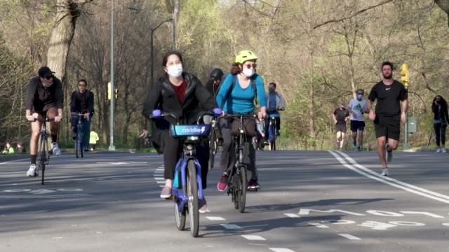 people jogging and cycling in manhattan's central park amid the outbreak of the coronavirus disease . some wearing face mask - protective workwear. - group of people stock videos & royalty-free footage