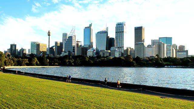People jogging in botanic garden in the morning with Sydney cityscape view