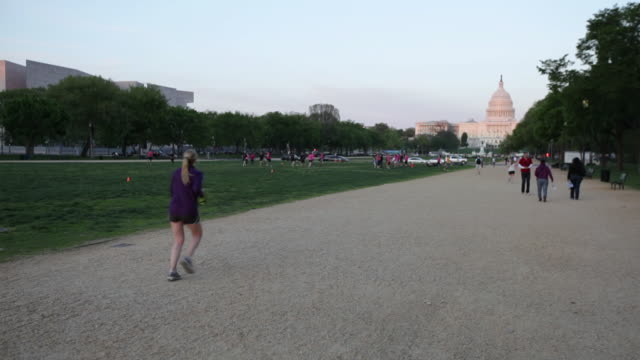 ws people jogging infront of capitol  building  / washington, district of columbia, united states - laufhose stock-videos und b-roll-filmmaterial