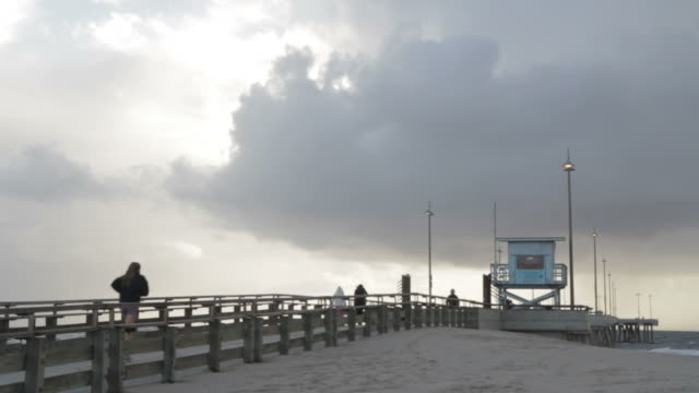 people jogging on beach pier while seagulls flying in - cabina del guardaspiaggia video stock e b–roll