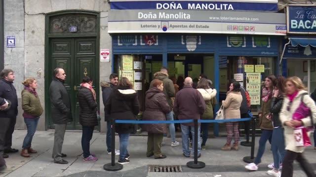 vídeos y material grabado en eventos de stock de people join a long queue to buy a ticket for the world's richest lottery at the famous dona manolita store in central madrid known for having sold... - artículos de lotería