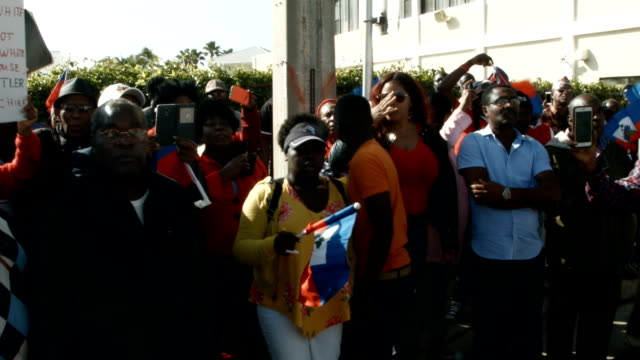 people join together near the maralago resort where president donald trump spent the last few days to condemn president trumps reported statement... - flag haiti stock videos & royalty-free footage