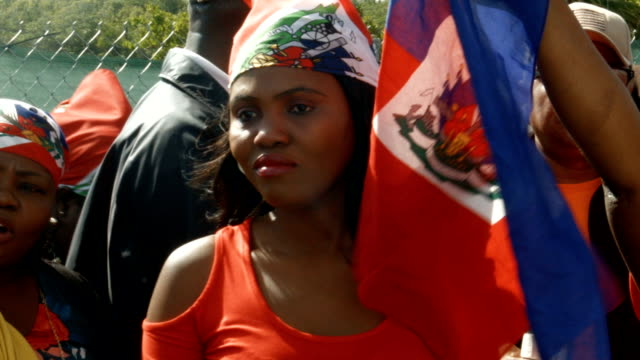 caption contains profanity people join together near the maralago resort where president donald trump spent the last few days to condemn president... - flag haiti stock videos & royalty-free footage