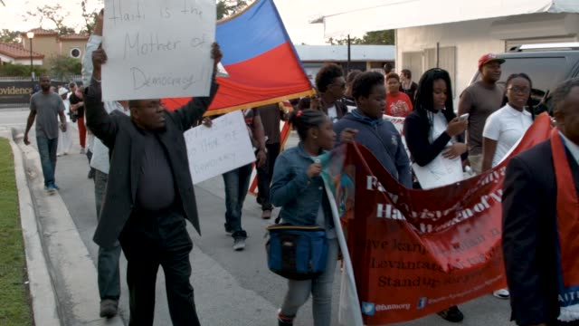 people join together to mark the 8th anniversary of the massive earthquake in haiti and to condemn president donald trump's reported statement about... - flag haiti stock videos & royalty-free footage