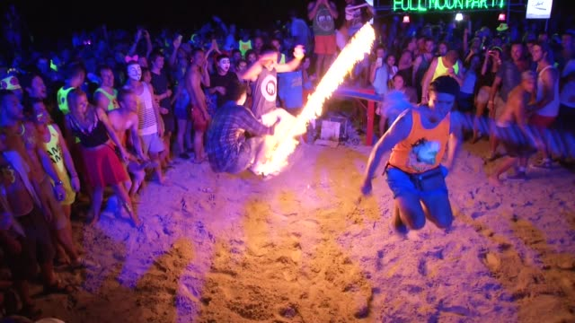 people jump a fire rope during the full moon party on the beach on ko phangan in thailand on jan 4 2015 - ko phangan stock videos and b-roll footage