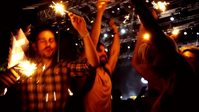 People jumping and dancing with sprinkle on concert