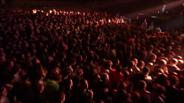 vídeos de stock e filmes b-roll de ws zi zo people jumping and moshing in middle of audience at large music concert / london, united kingdom   - film festival