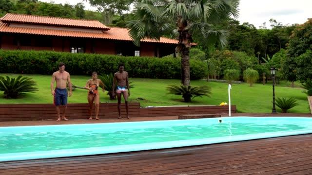 vídeos de stock, filmes e b-roll de pessoas pulando na piscina - piscina
