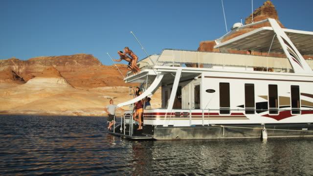 vidéos et rushes de people jumping off a houseboat - red rocks